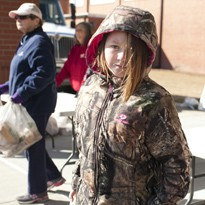 Girl in camo hoodie stands outside during volunteer day