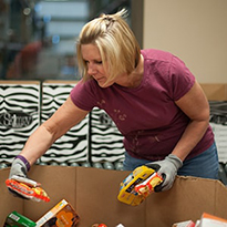 Woman sorts through food items during a volunteer opportunity
