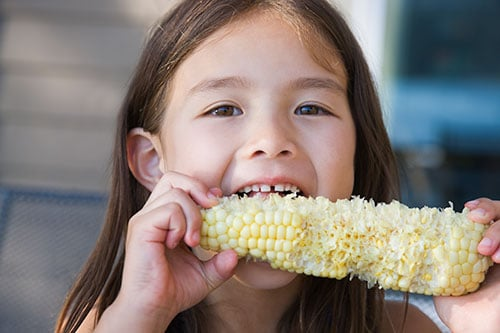 Girl eating corn.