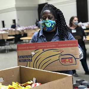 Volunteer wearing face mask and moving boxes at food bank