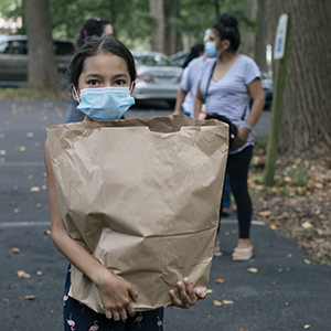 Young girl holding groceries from food bank while wearing a mask