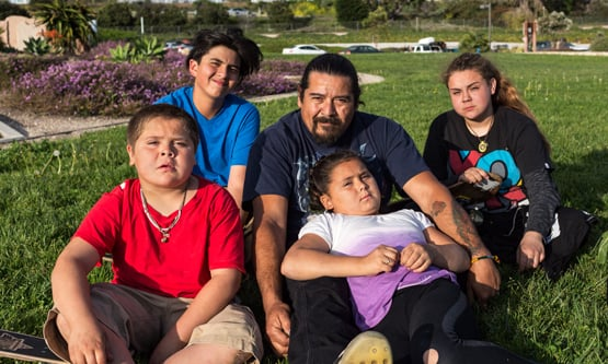 Manny and four children sitting on grass