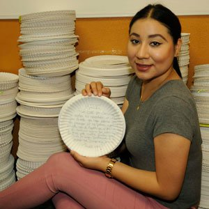 Elizabeth Benitez with plates she translated.