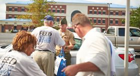A member of the military volunteers distributing food.