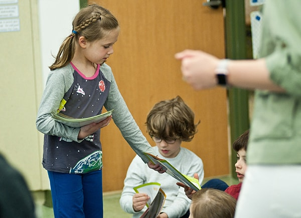 A second grader hands out materials from the Hungry to Help lesson to her classmates.