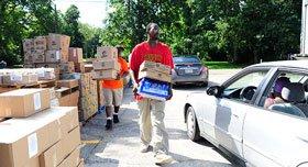 Volunteers distribute disaster relief boxes.