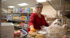 A woman volunteering at a food pantry