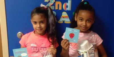 Two girls hold Valentine's cards.