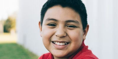 Julio, 12 year old, wearing a red shirt and smiling outside a food bank