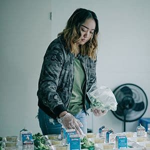 Volunteer preparing dinner for children at a food pantry