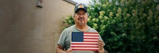 Julio, a veteran, holding an American flag outside a food pantry