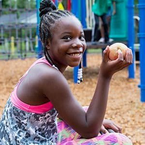 Girl holding an apple on a playground