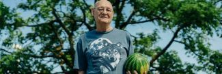 Older man at senior food pantry holding a watermelon