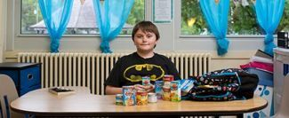 Boy at table with food he receive from his school pantry