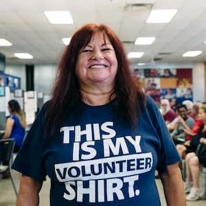 "Woman wearing a blue ""This is my volunteer shirt"" t-shirt."