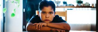 9-year-old Deron sitting at dining room table looking sad