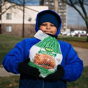 Child wearing winter coat holding Thanksgiving turkey