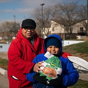 Child and parent wearing winter coats and holding turkey they received from food bank