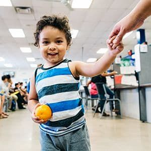 Juan Alfredo, 2, eats an orange at a summer meals program in Phoenix, Arizona.