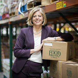 Katie Fitzgerald wearing purple suit in food bank warehouse
