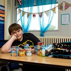 Lucas wearing Batman t-shirt with food from the school backpack program