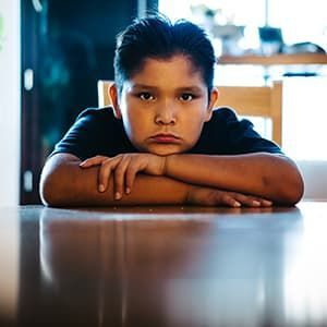 Deron, age 9, wearing black t-shirt and sitting at kitchen table