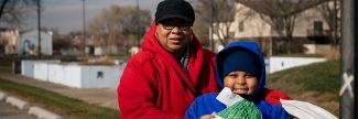 Jaylen, age 8, with grandmother at Thanksgiving food pantry distribution