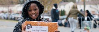 Alayaha in a polka dot coat holding a Thanksgiving Dinner box