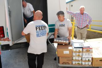 Food Lion volunteers carrying loading food bank truck