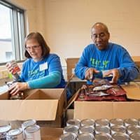 Two volunteers packing food at food bank