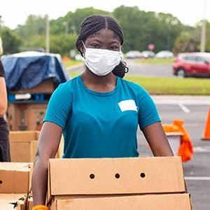 Food bank volunteer carrying boxes