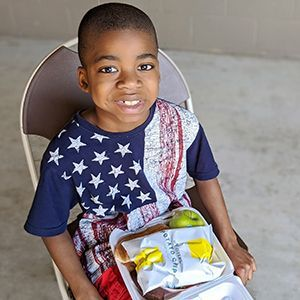 Boy wearing America flag t-shirt with donated meal of chips, apple, and sandwich