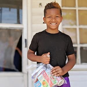 Child standing on porch holding food from food pantry