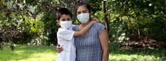 Mother and son hugging outside while wearing masks