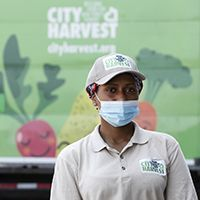 Food bank driver wearing uniform with City Harvest logo in front of truck that says City Harvest