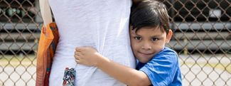 Boy hugging his mother at a mobile food pantry