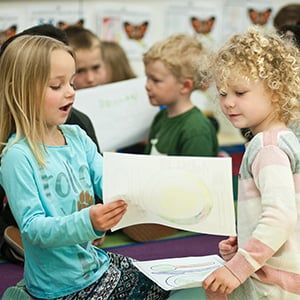 Two young girls talking about their drawing.