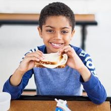 8-year-old Mateo eats lunch at Blackhawk Park, a summer meals site in Aurora, Illinois.