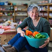 Lynn, a volunteer at a food bank, holding bell peppers