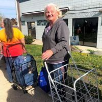 Elderly woman waiting in line at food bank with cart