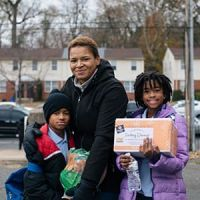 Carmen and her 7-year-old son Cameron and 10-year-old daughter Laila receive a Thanksgiving turkey and sides from a holiday food distribution at the children's school in Philadelphia.