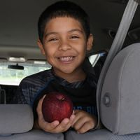 Boy in back seat of car holding apple and smiling